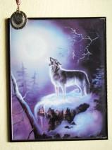 Winterlandschaft. Ein Wolf steht auf einem verschneiten Vorsprung und heult den Mond an