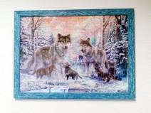 Zwei Wölfe plus vier Welpen in winterlicher Waldlandschaft