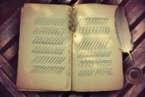 Altes Buch mit Schreibübungen in schönes Schreibschrift. Daneben Federkiel und Tintenfass.
