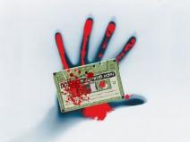 Blutige Hand an einer Scheibe o.ä. mit blutiger Musikassette