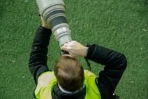 Fotograf mit großen Teleobjektiv am Spielfeldrand eines Fußballspiels