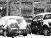 Verschneite Autos durch verregnete Scheibe fotografiert