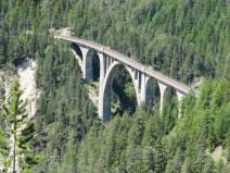 Eine sehr hohe Brücke in den Bergen. In der Schlucht und drum herum unzählige Bäume.