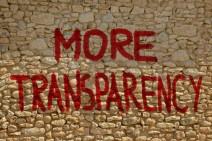 """Sandfarbene Steinmauer, auf die in roter Farbe und Großbuchstaben """"more transparency"""" geschrieben wurde."""