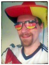Foto von mir Cowboyhut und Sonnenbrille in schwarz, rot, gold. Dazu ein paar passende Tattoo-Sternchen und die Fahne ins Gesicht geschminkt. Last but not least das Trikot.