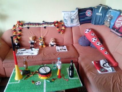 Foto: Couch-Ecke, auf jedem Platz das passende Trikot für die Familienmitglieder. Papiertischdecke im Fußballfeld-Design. Jede Menge Utensilien wie Tröten, eine Trommel.