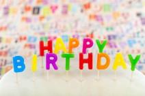 """Foto: Buchstabenkerzen bilden den Schriftzug """"Happy Birthday"""" auf einer Torte"""