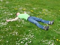 Mann liegt - alle Viere von sich gestreckt - auf einer grünen Wiese
