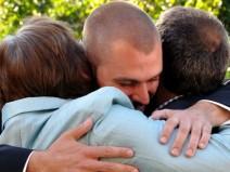 Junger Mann umarmt innig zwei ältere Menschen als er selbst. Es sieht so aus, als wären es seine Eltern. Ob Freude oder Leid der Anlass ist, kann man nicht exakt erkennen.