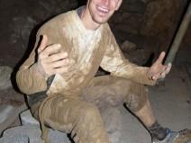 Foto: Ein Mann, vollkommen eingesaut mit Schlamm, sitzt auf Steinen und grinst in die Kamera, als hätte er noch nie etwas schöneres erlebt.