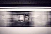 Schwarz-Weiß-Foto: Werbeplakate durch einen vorbeirauschenden Zug hindurch fotografiert