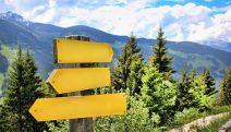 Wegweiser mit mehreren richtungsweisenden Schildern. Im Hintergrund Berglandschaft.