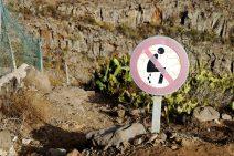 Foto von einem Schild, auf dem das Verrichten eines großen natürlichen Geschäftes im Freien verboten wird