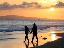Foto eines Pärchens, dass den Sonnenuntergang bei einem Strandspaziergang genießt