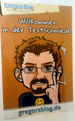 """Ein Poster im Layout des Blogs mit meinem Comic-Ich und der Aufschrift """"Willkommen in der Textschmiede"""""""