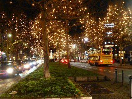 Foto vom Kurfürstendamm in der Adventszeit. Die Bäume sind mit Lichterketten geschmückt.