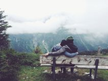 Foto von einem Paar auf einer Bank mitten in den wolkenverhangenen Bergen