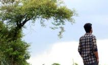 Foto: Mann ist von hinten zu sehen. Er steht in der Natur und schaut in die Ferne.