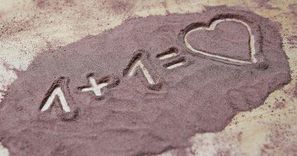 Foto: Sand auf dem Boden. In den Sand gemalt steht dort 1 + 1 = Herz