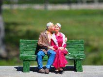 Foto von einem Paar im hohen Alter. Sie sitzen auf einer Bank. Er hat den Arm um sie gelegt und gibt ihr einen Kuss auf die Wange.