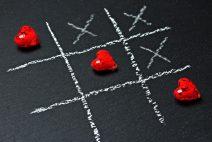 Foto von einem Käsekästchen-Spiel: Herzen gewinnen gegen Kreuze.
