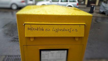 Foto von einem öffentlichen, gelben Briefkasten. Auf der Einwurfklappe steht: Hoffentlich ein Liebesbrief