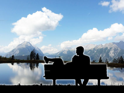 Schattenhafter Umriss eines Pärchens auf einer Bank vor Alpen-Panorama