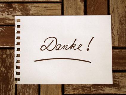 """Ein Zettel mit dem Wort """"Danke"""" darauf auf einem hölzernen Hintergrund"""